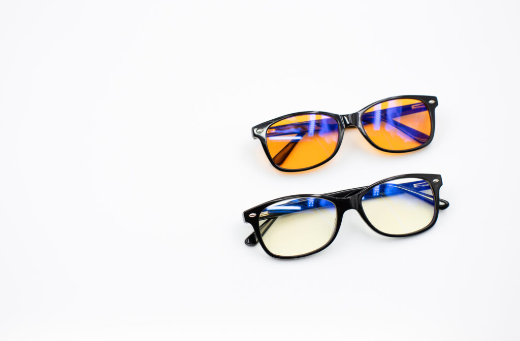 A pair of blue light glasses that have been set down on a white background.