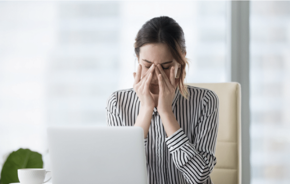A woman sitting in front of a laptop computer, that is rubbing her eyes and the ridge of her nose in pain.